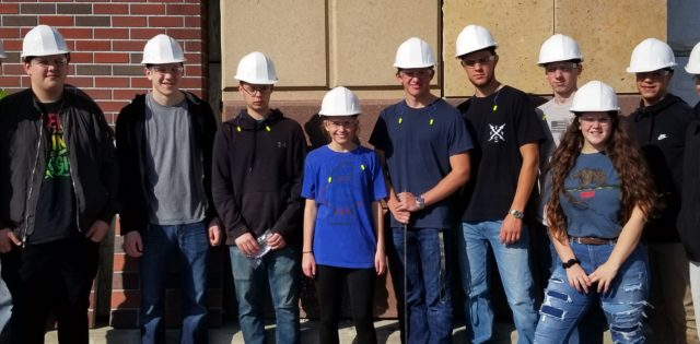 Students in white hard hats standing in front of a brick and concrete facade.