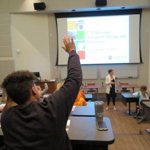 image of a student raising thier hand in a lecture hall.